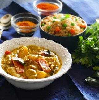 Instant Pot Thai Yellow Curry with Chicken in white bowl on blue napkin, with fried rice in another bowl