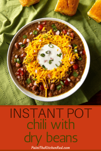 Instant Pot Chili Pinterest pin with image of chili with shredded cheddar surrounding sour cream, topped with green onions. On a green cloth with pieces of corn bread. From Paint the Kitchen Red