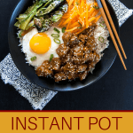 Instant Pot Korean Beef pinterest - rice bowl with beef, fried egg, carrots, greens in black bowl with chopsticks - Paint the Kitchen Red