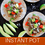Instant Pot Pork Carnitas Pinterest - three tortillas with meat, avocado, tomato, cilantro and cheese laid out with cut avocado and lime on the side- Paint the Kitchen Red