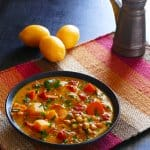 Vegetarian Instant Pot Moroccan Stew with carrots, squash, chickpeas, cilantro, tomatoes in black bowl on colorful mat with lemons in background