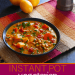 Vegetarian Instant Pot Moroccan Stew Pinterest image - stew with carrots, squash, chickpeas, cilantro, tomatoes in black bowl on colorful mat with lemons in background