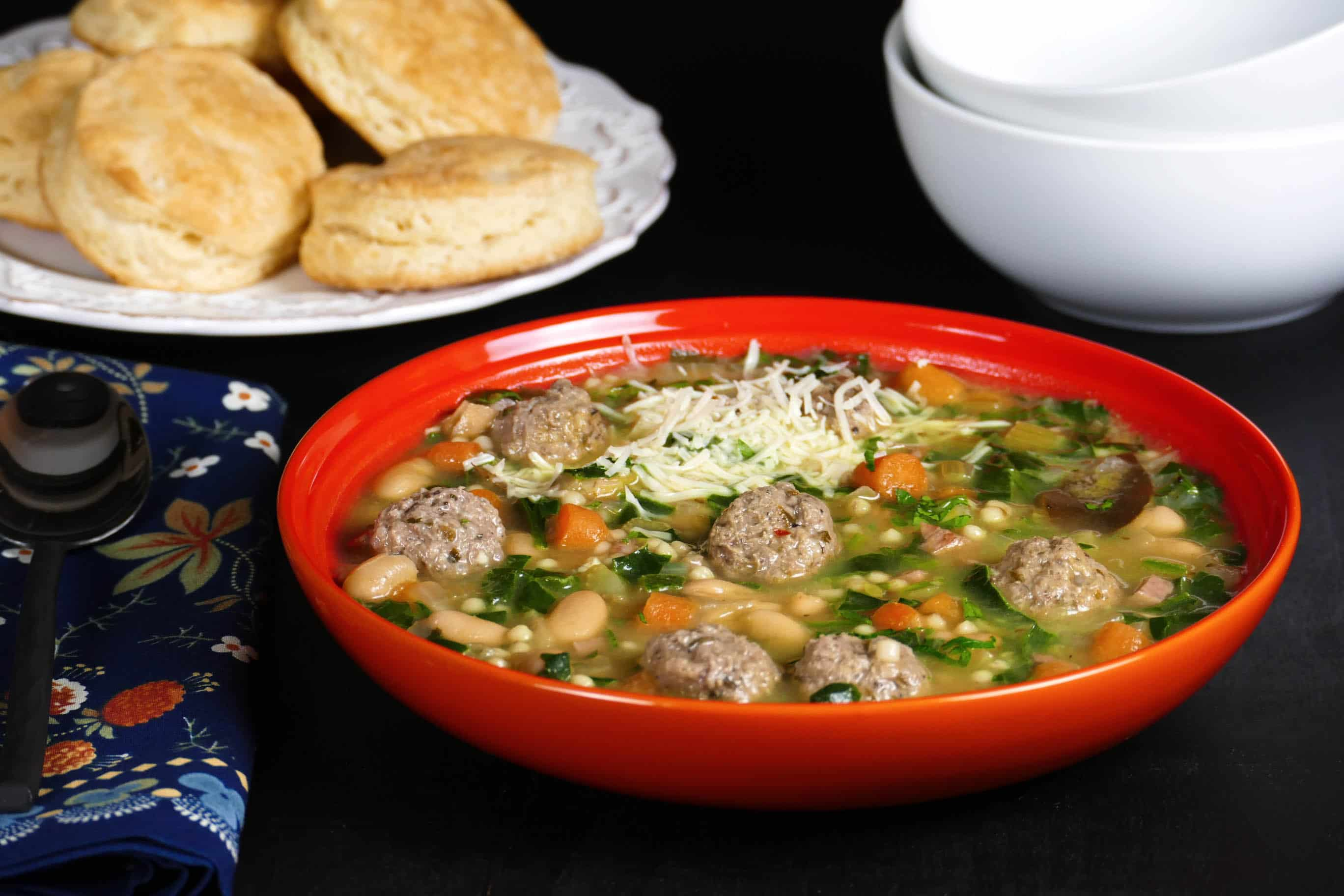 Instant Pot Italian Wedding Soup - Orange bowl with beans, carrots, meatballs, spinach, parmesan and bread and empty bowls in the background - Paint the Kitchen Red