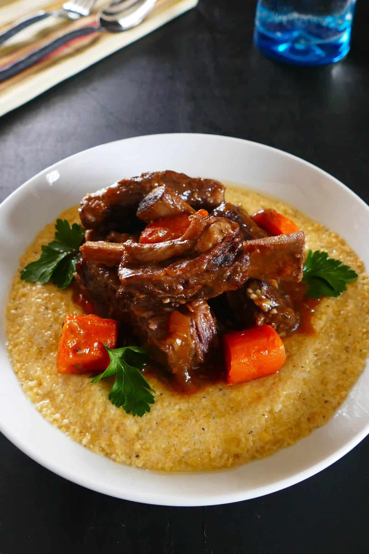 Instant Pot Short Ribs in white bowl over polenta, with carrots