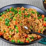 Instant Pot Brown Fried Rice L1 - black bowl of fried rice with carrots peas and green onions with a serving spoon in the middle of bowl - Paint the Kitchen Red
