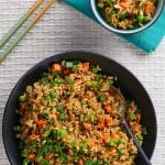 Instant Pot Brown Fried Rice P1 - black bowl of fried rice with carrots peas and green onions with a serving spoon in the middle of bowl - Paint the Kitchen Red