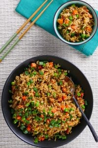 Instant Pot Brown Fried Rice P1 - black bowl of fried rice with carrots peas and green onions with a serving spoon in the middle of bowl