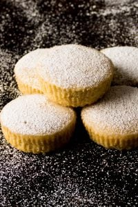 Instant Pot Cupcakes Cardamom Pound Cakes stacked on a black background and dusted with confectioners sugar - Paint the Kitchen Red