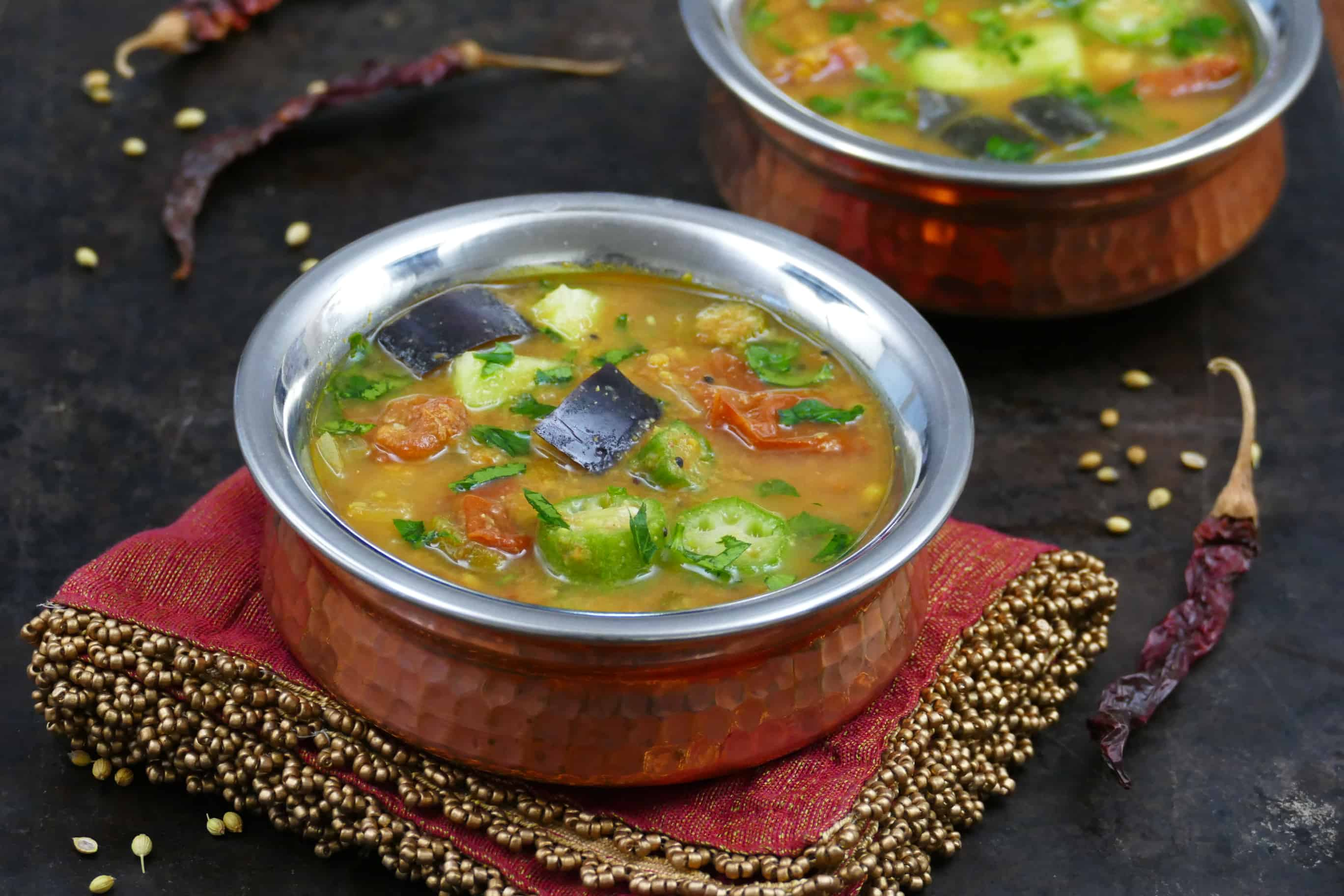 Instant Pot Sambar L1 - two bowls of sambar with tomatoes, eggplant okra, garnished with cilantro - Paint the Kitchen Red
