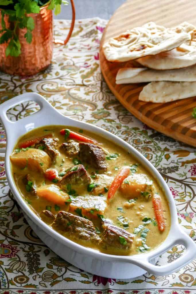 Instant Pot Beef Curry in white oval serving dish with cilantro and naan in the background - Paint the Kitchen Red.jpg