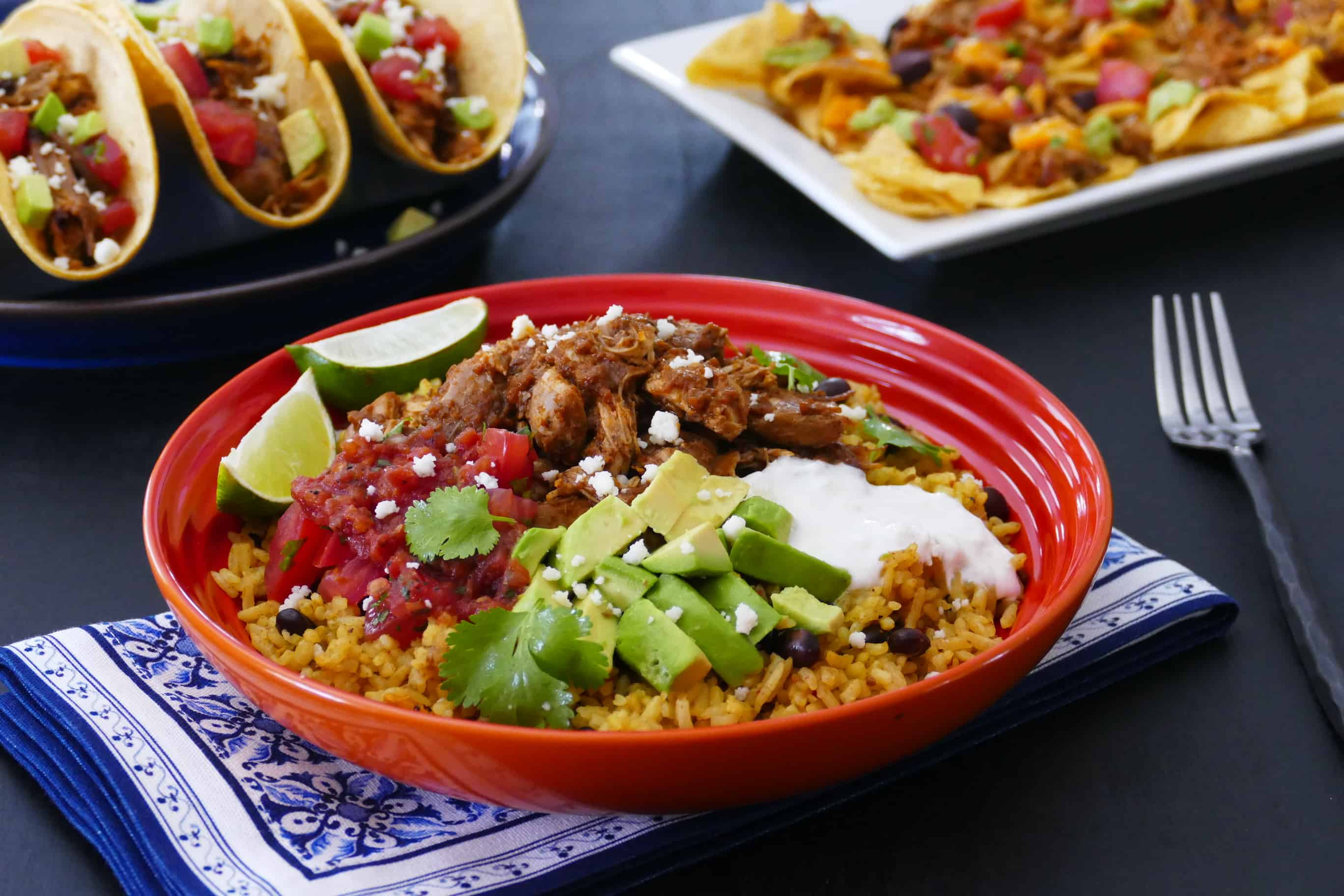 Instant Pot Chicken Tinga rice bowl in orange bowl with chicken tinga tacos and nachos in the background - Paint the Kitchen Red