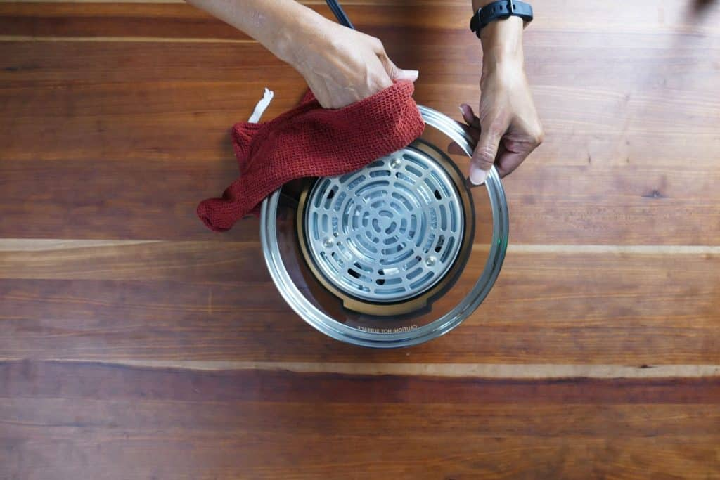 Damp red cloth being used to wipe the upside down Mealthy CrispLid - Paint the Kitchen Red