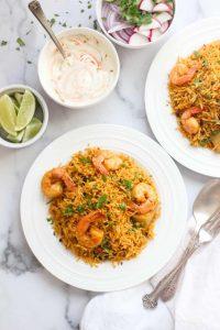 Instant Pot Shrimp Biryani - 2 plate with raita, lime and garnish on the side