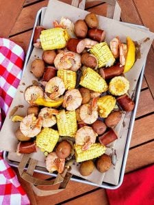 Tray lined with paper and boiled shrimp, potatoes, sausage, corn