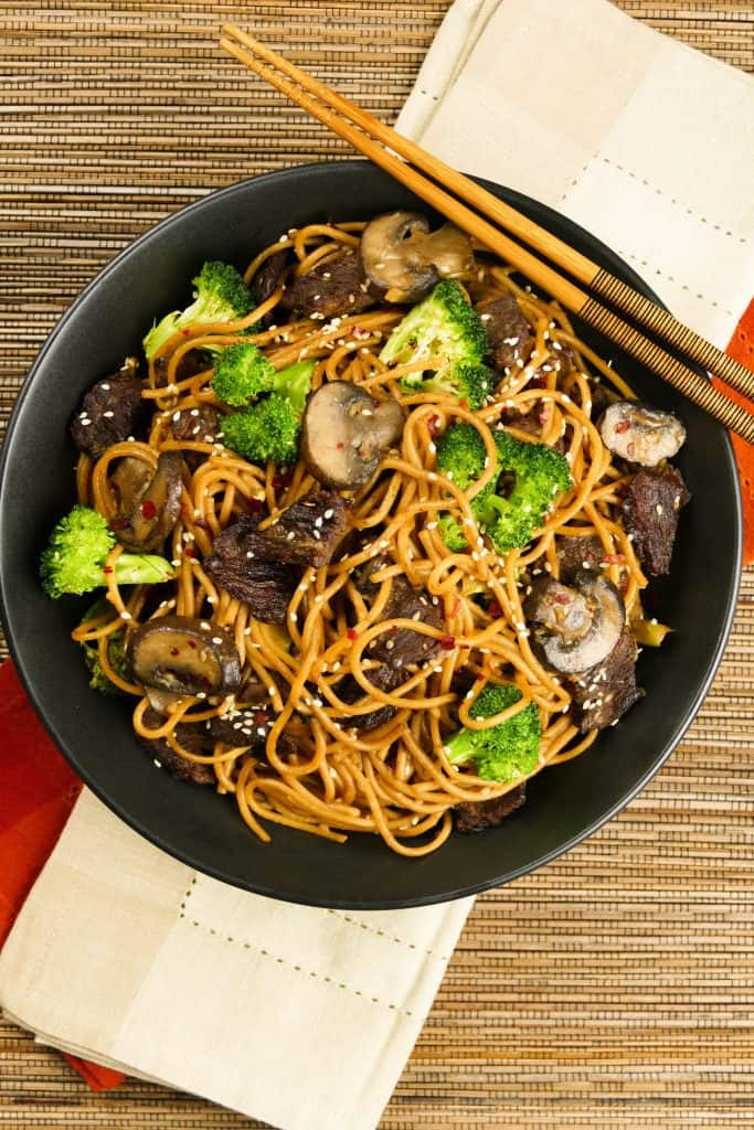 Instant Pot Lo Mein with Beef and Broccoli in black bowl on straw mat with chopsticks laid across bowl - Paint the Kitchen Red
