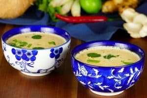 2 Asian-print bowls of Instant Pot Thai coconut soup with herbs in the background