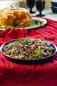 Instant Pot Wild Rice Pilaf topped with pecans and dried cranberries in a blue bowl on a festive red tablecloth- Paint the Kitchen Red