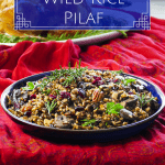 Instant Pot Wild Rice Pilaf Pinterest Pin - rice topped with pecans and dried cranberries in a blue bowl on a festive red tablecloth- Paint the Kitchen Red
