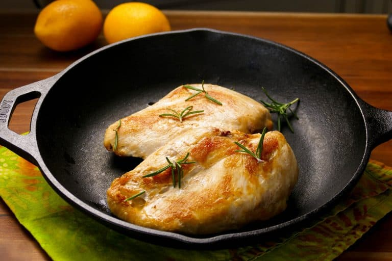 2 Sous Vide Chicken Breasts in a cast iron pan with lemons in the background- Paint the Kitchen Red