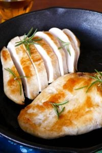 1 whole and one cut up Chicken Breast with rosemary in a cast iron pan with lemons in the background- Paint the Kitchen Red