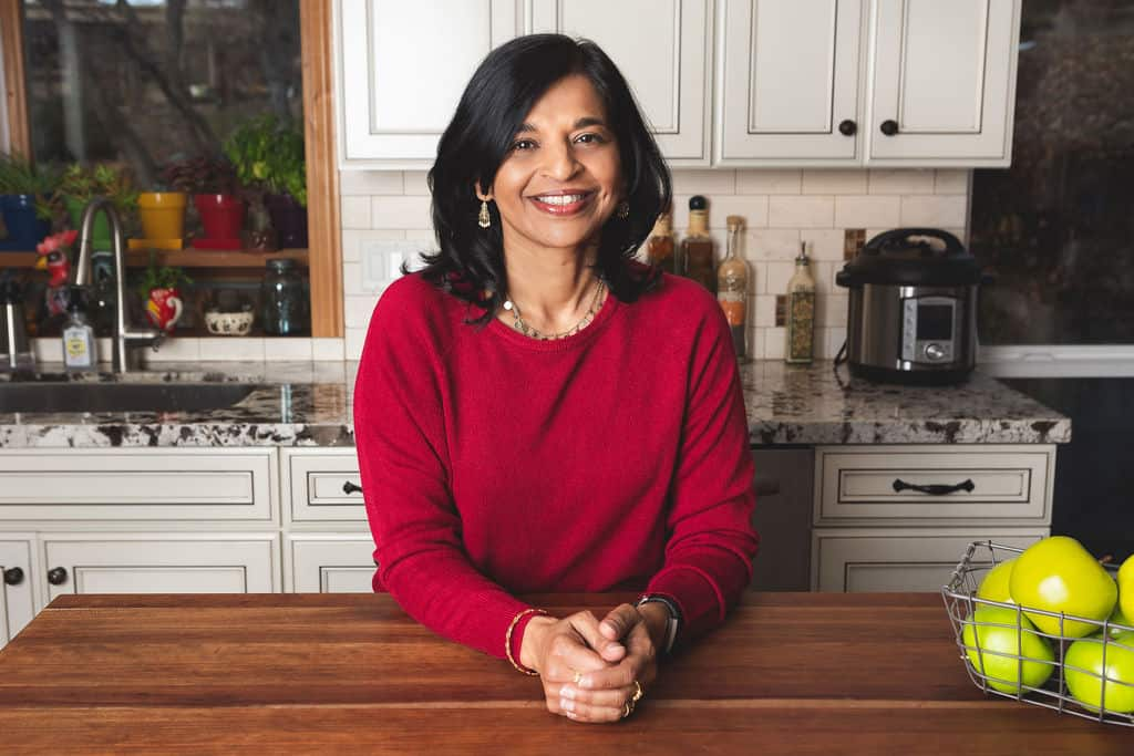 Neena in red sweater in a white kitchen leaning on the counter - Paint the Kitchen Red