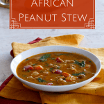 Instant Pot African Peanut Stew Pin - stew in a white bowl with cut sweet potato, peanuts and cilantro in background