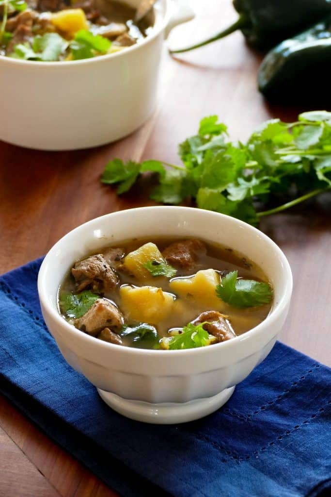 Instant Pot Pork and Hatch Chile Soup in a white bowl on a blue napkin