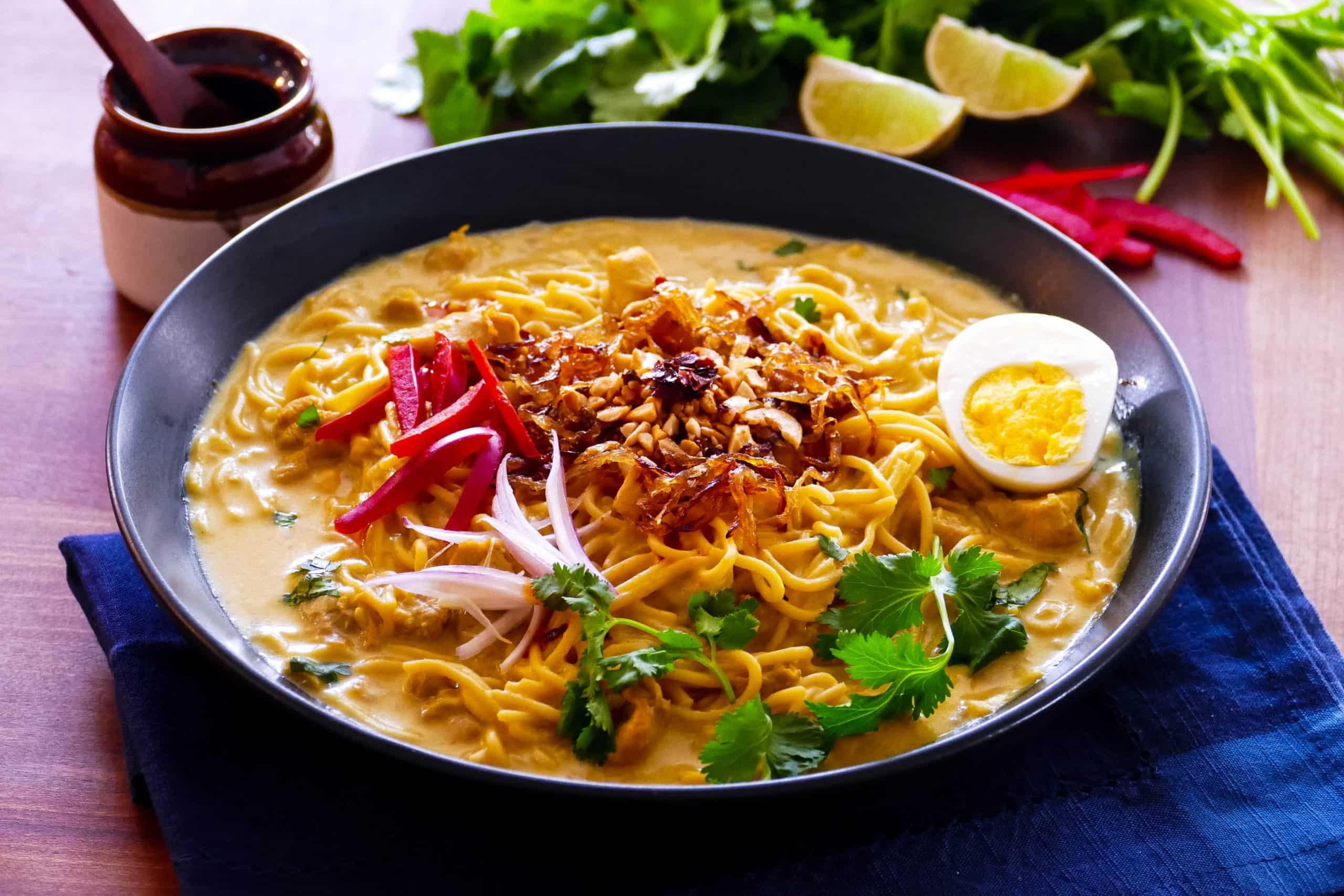 Instant Pot Khao Suey - Burmese noodles in coconut curry broth topped with fried onions, garlic, boiled egg and cilantro
