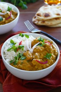 Instant Pot chicken korma curry with rice in a bowl with naan bread in the background