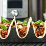 Three Instant Pot Pulled Pork Tacos on a table