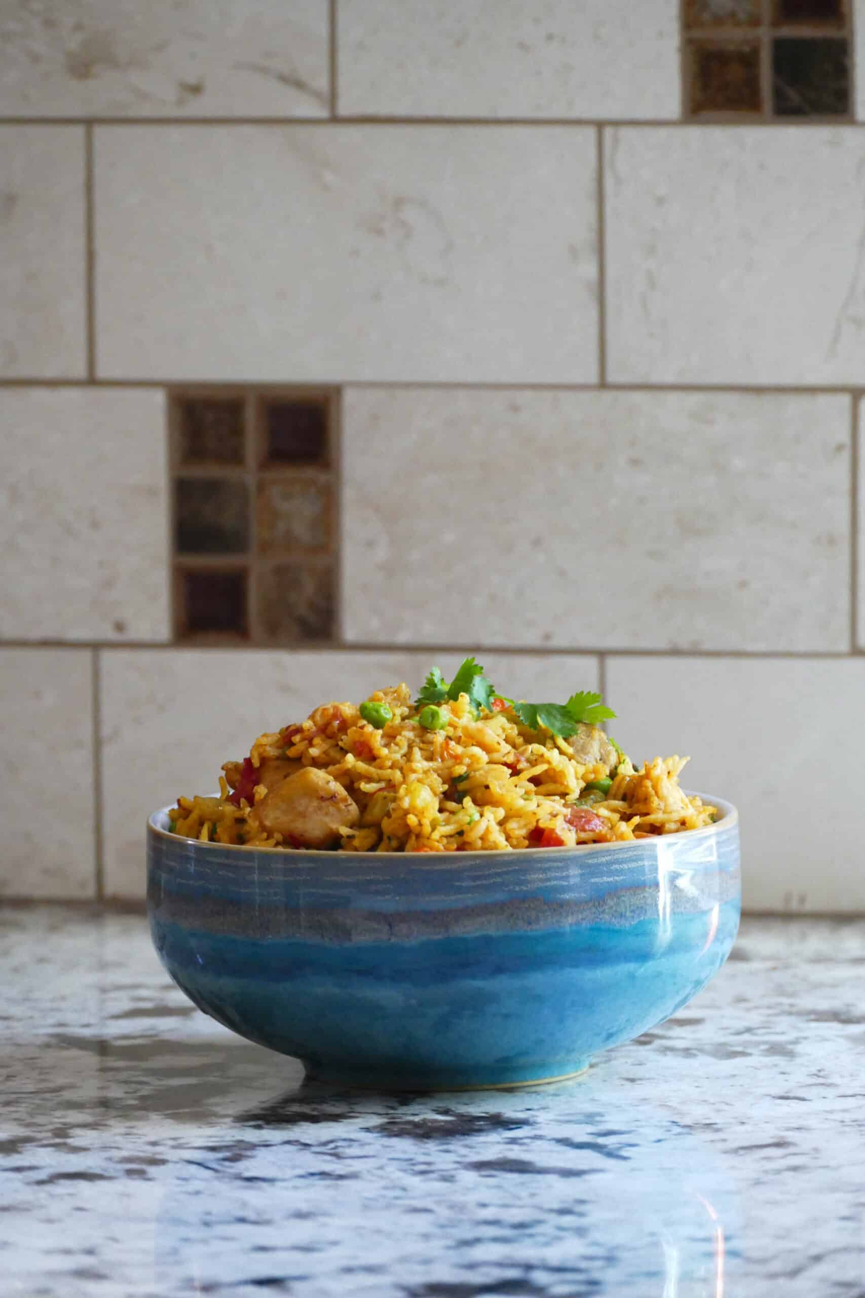 Blue bowl on counter with yellow rice, peas, chicken topped with cilantro