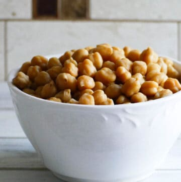 A bowl of cooked chickpeas on a white counter
