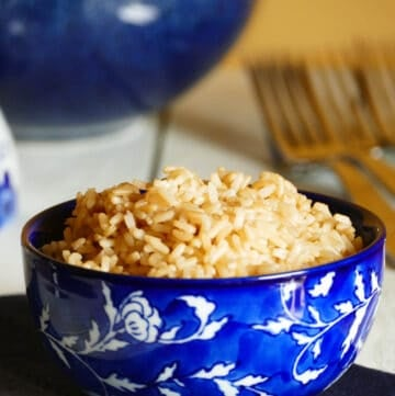 Parboiled brown rice in a blue bowl with a larger bowl of rice in background