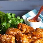 Instant Pot Korean Chicken two thighs and four drumsticks on a dark background, garnished with sesame seeds