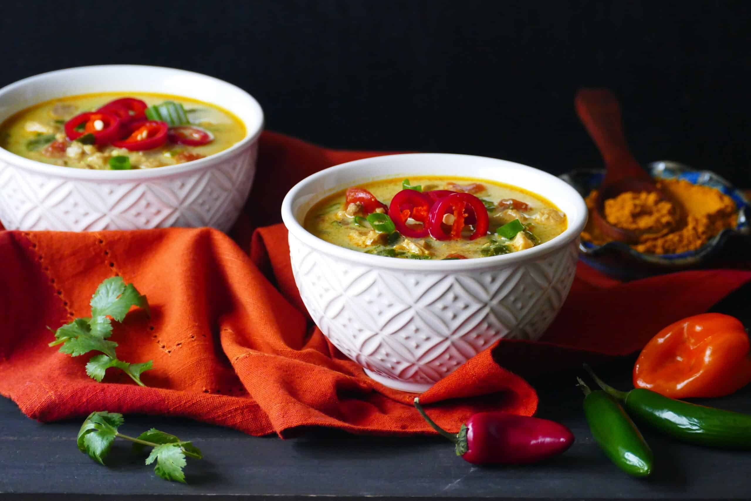 Two white bowls of yellow colored chicken curry soup garnished with red jalapenos and green onions on an orange napkin