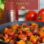 Instant Pot chorizo and potato Pinterest pin - Black round serving dish with chorizo and potato sprinkled with cilantro and copper mug with fresh cilantro and fresh tomatoes in background