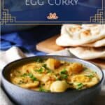 Pinterest pin with Blue speckled bowl of egg curry garnished with cilantro, with another bowl of curry, naan and brown eggs in the background