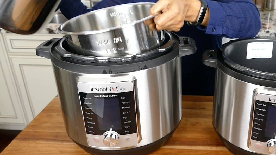 Two instant pots on a counter. 6 quart inner pot being put into 8 quart Instant Pot