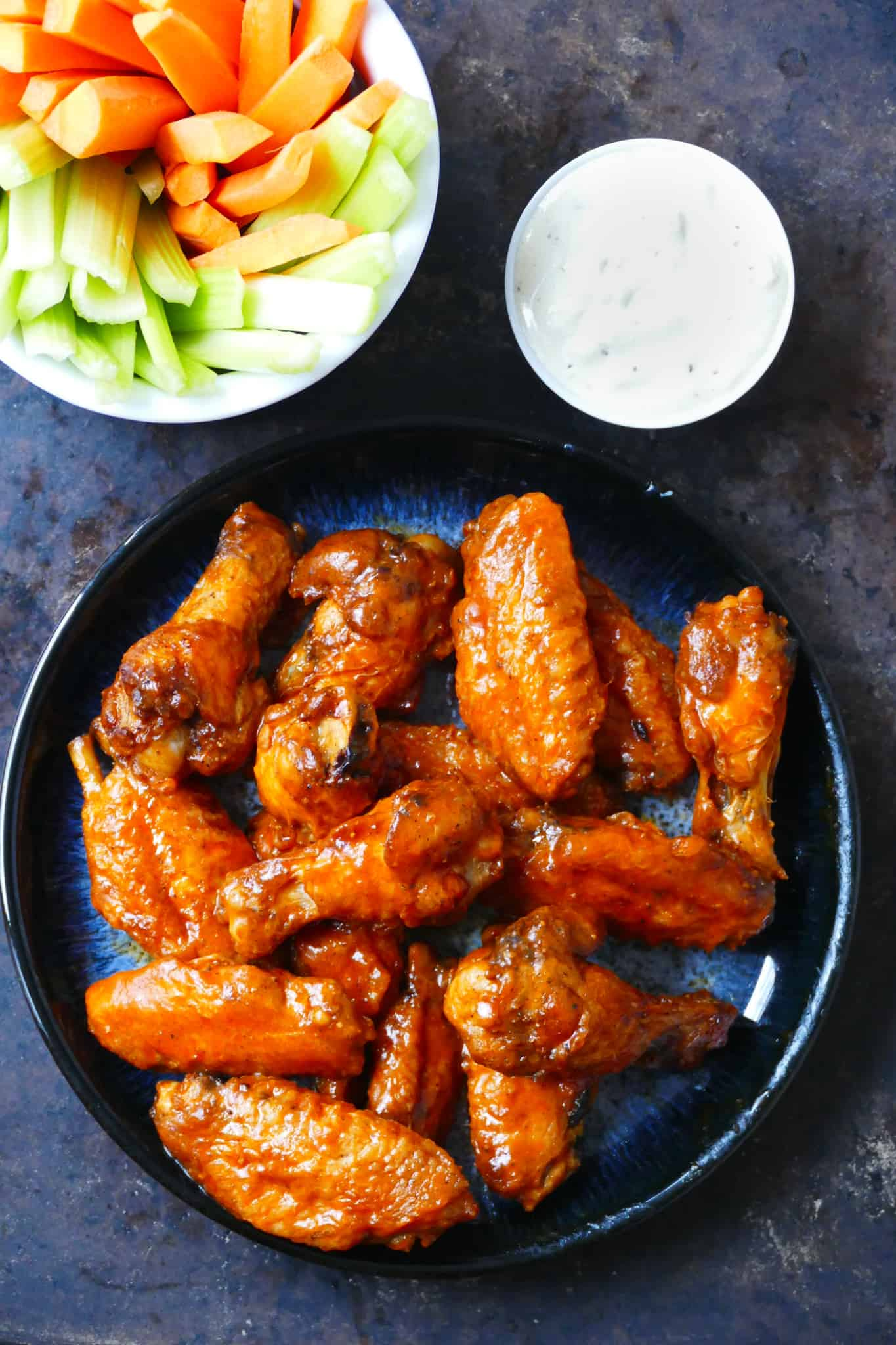 Blue plate with hot wings glistening with sauce and carrots, celery in a white bowl and ranch sauce in a bowl