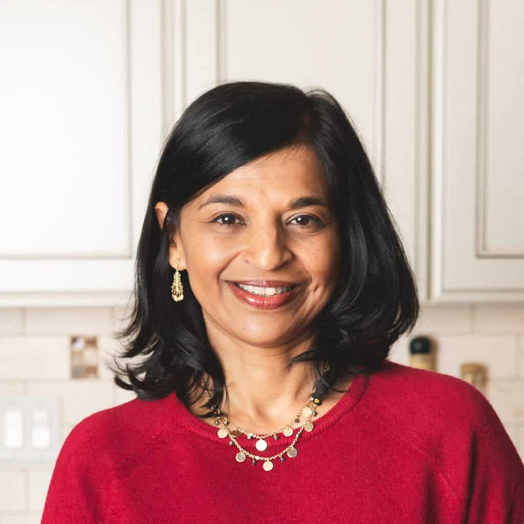 Neena in red sweater slight smiling with white cabinets in background
