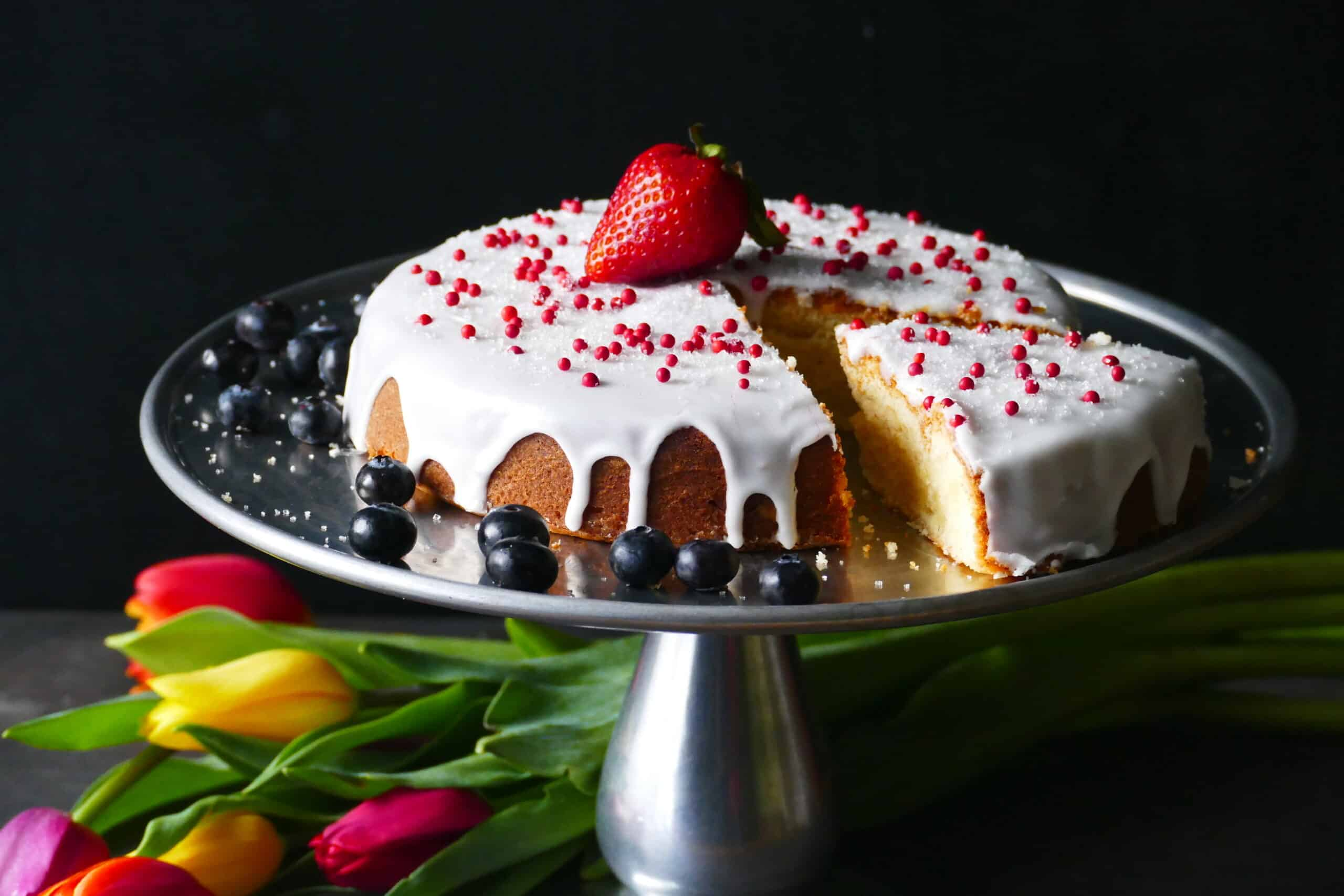 Pound cake on cake stand frosted with white frosting and topped with red balls and a ripe strawberry and blue berries on the side