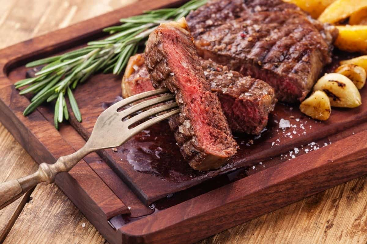 beef steak cut into slices with potaotes on a wooden board