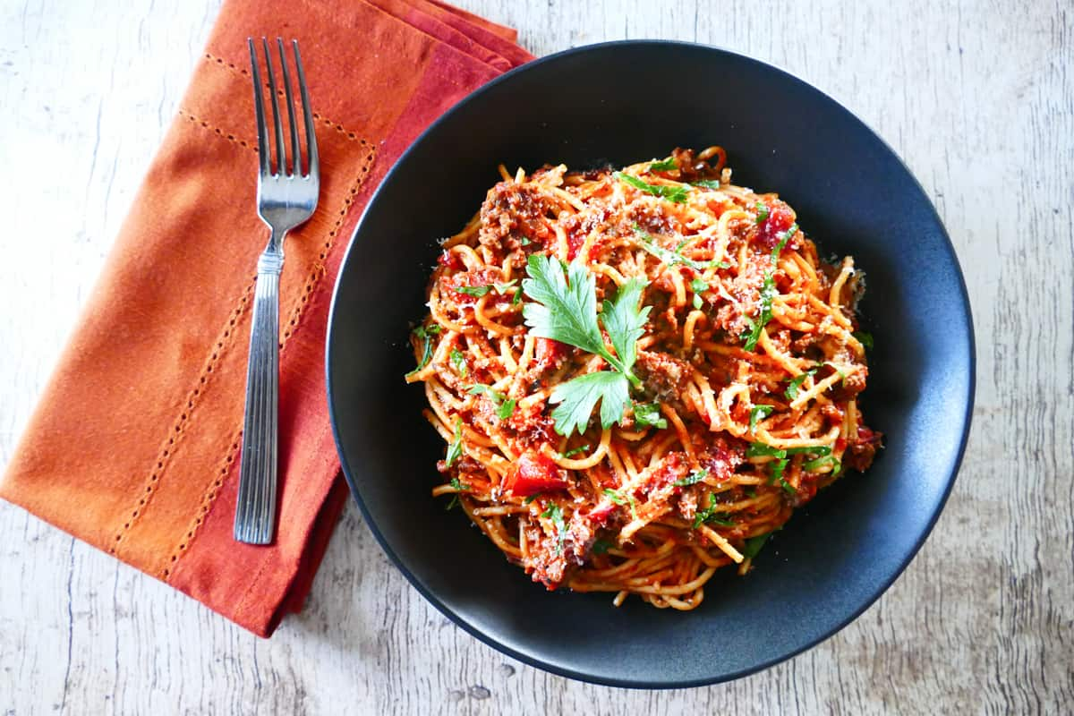 Instant Pot Spaghetti and Meat Sauce in a black bowl and wood background; napkin with bread on the side - Paint the Kitchen Red