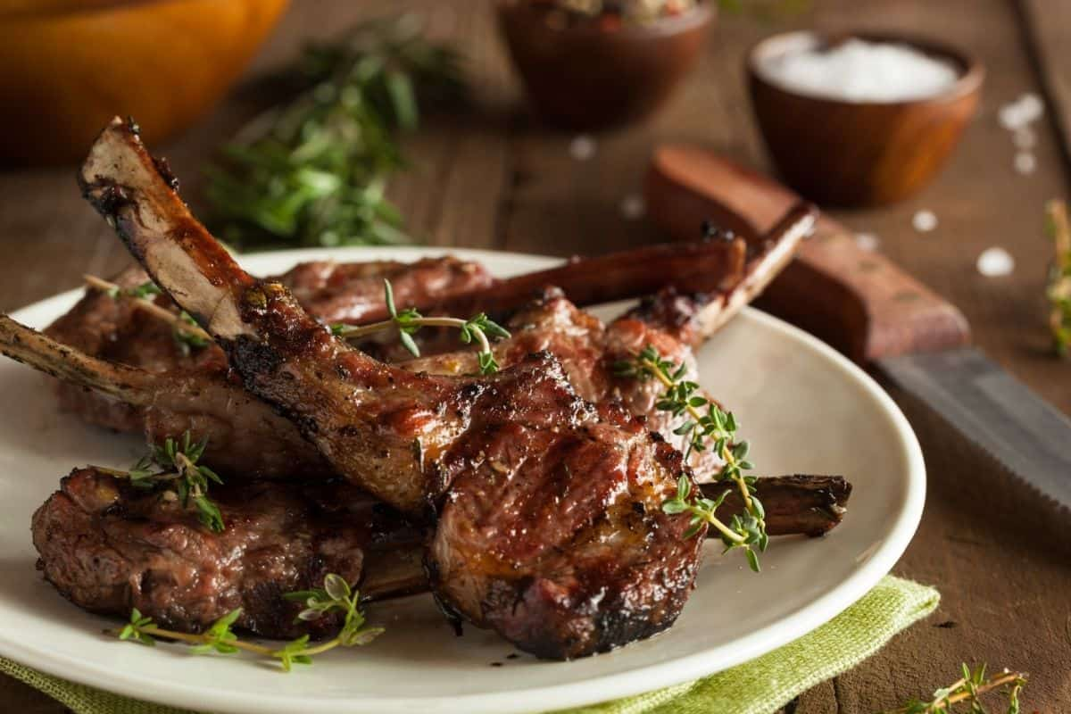lamb chops on a white plate garnished with thyme