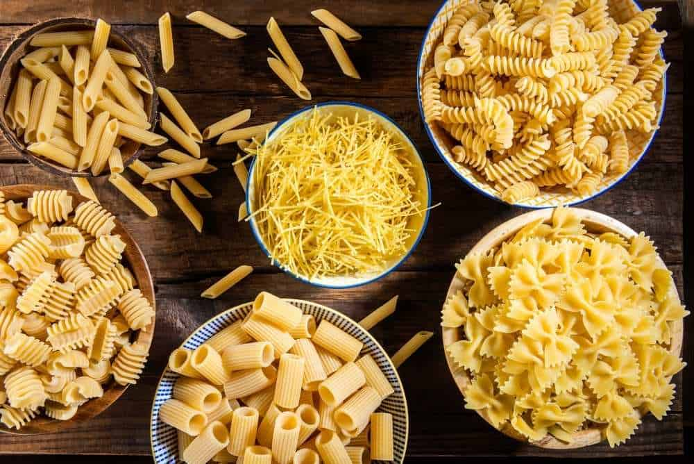 Assorted pastas in bowls including rotini, farfalle, penne, rigatoni