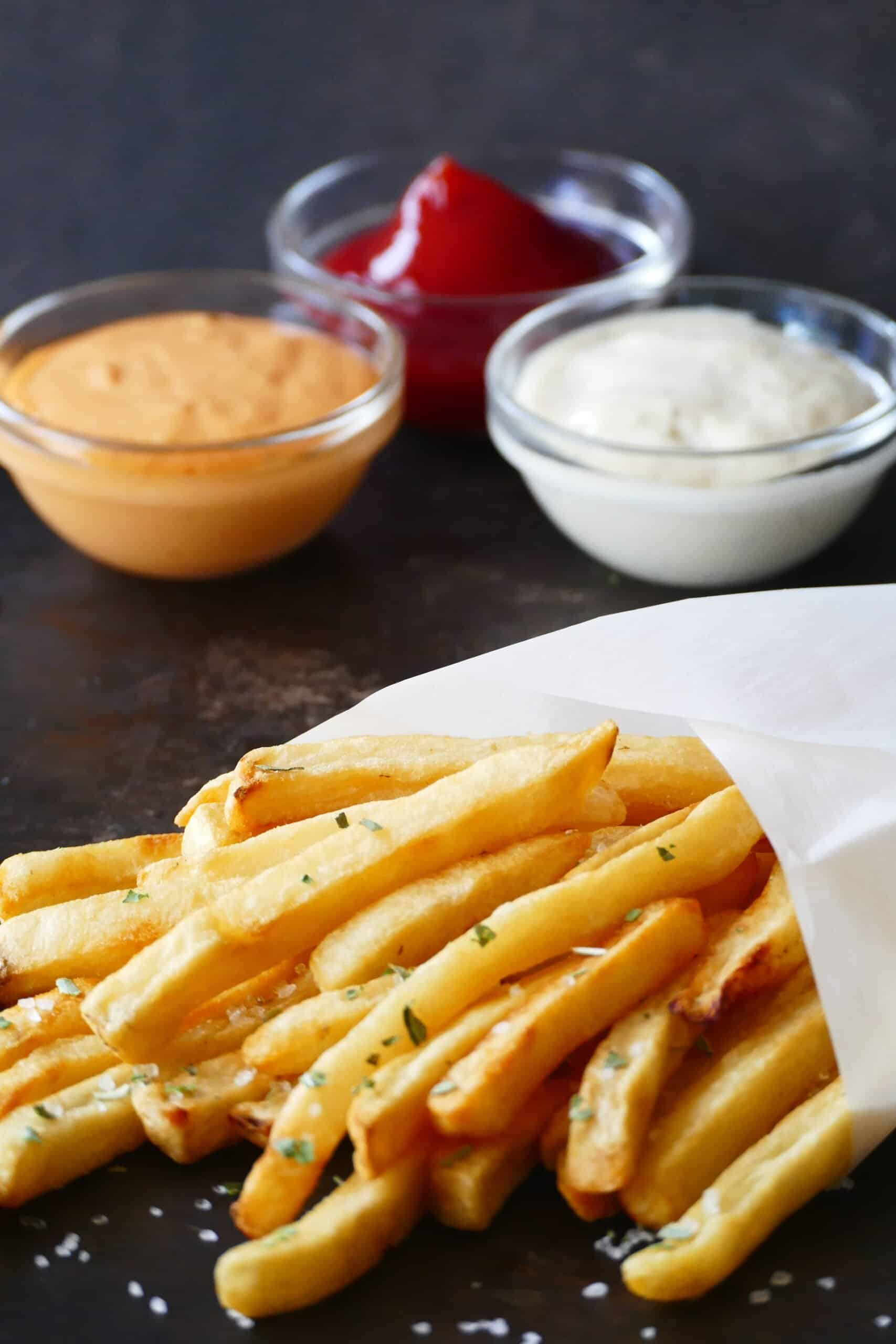 French fries with sea salt and parsley wrapped in white parchment and three glass bowls with condiments